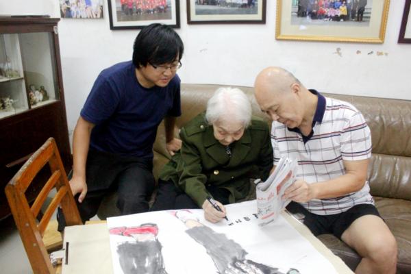 程俊老战士在画上签名(周茜 拍摄)