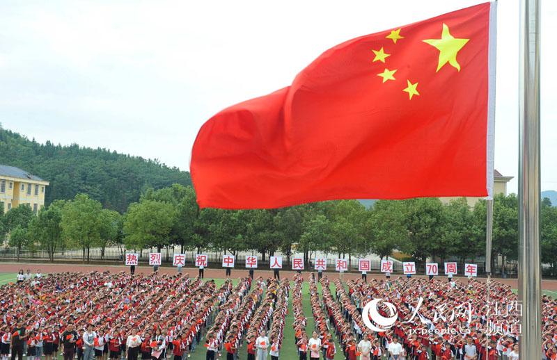 1500余留守儿童开心地挥舞着国旗,同唱《我和我的祖》。