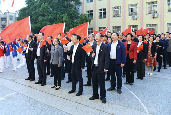 与会人员参加湖滨小学升旗仪式,与小学生们一起共唱《我和我的祖国》