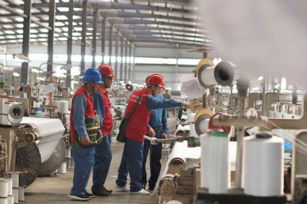 国网抚州供电公司员工在江西金武纺织有限公司车间为客户提供安全用电指导,介绍购售同期业务。(钱婷摄影)