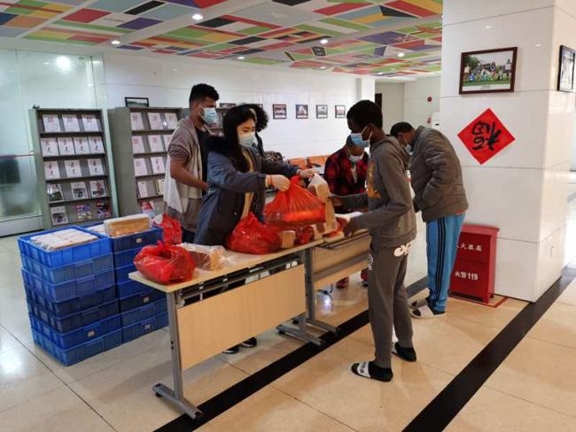 1左二为李妍婷老师,正在为留学生分配食物
