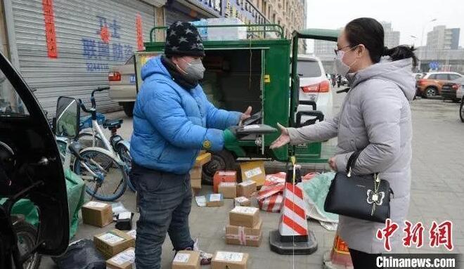 图为快递工作人员在小区口围起来一小片区域,收发快递。 刘文华 摄