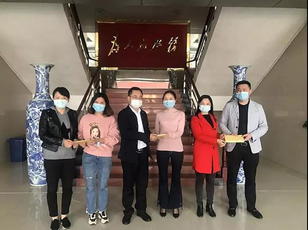 党委副书记、管委会主任沈乐将爱心捐款送到社区负责人手中