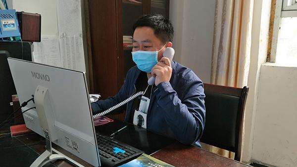 金山镇信访办李文志正在电话回访上访群众