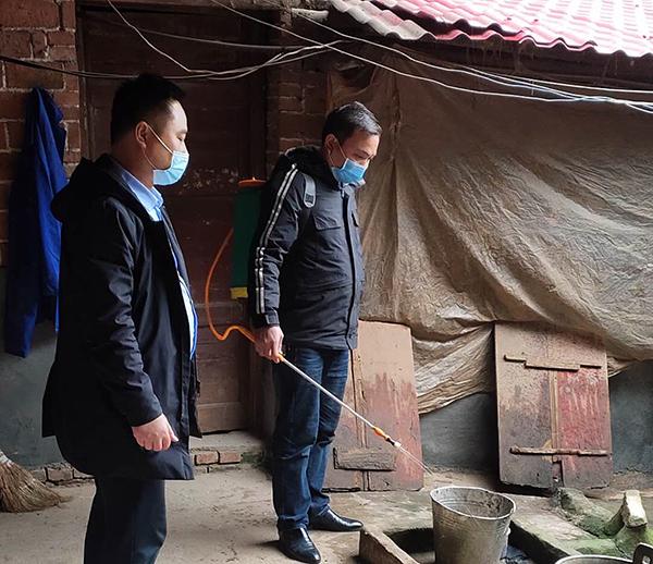 街农办工作人员与驻村第一书记帮助阳付益做好消杀工作