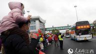 机场外欢迎医护人员的群众排成长队。图为一名小女孩骑在爸爸肩上和援助武汉的医生妈妈隔窗打招呼。时雨/摄