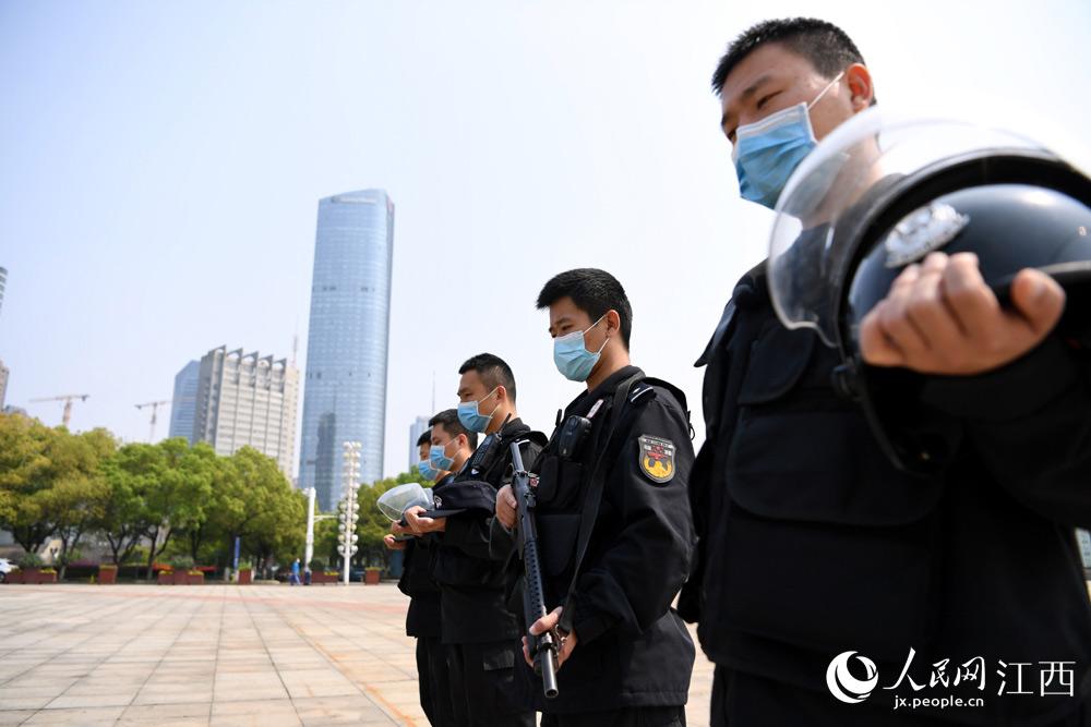 南昌市公安局特警支队七大队巡逻民警在路边驻足向英雄致敬,向逝者志哀。(时雨/摄)