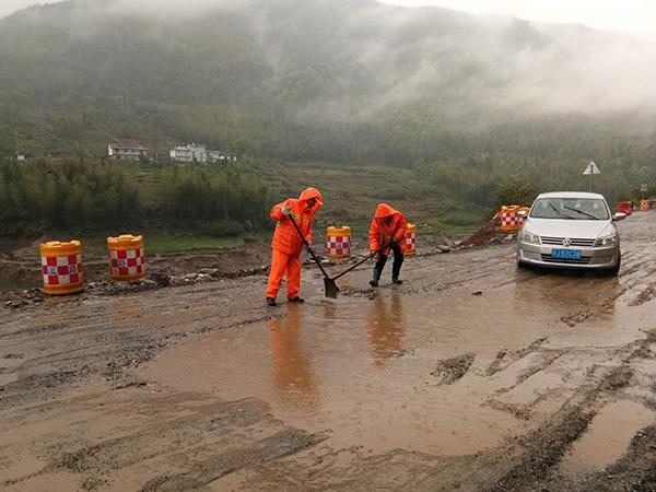 风雨中,芦溪公路人正在533省道坑口路段排除路面积水。