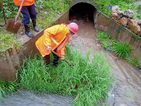风雨中,芦溪公路人正在320国道芦溪段疏通涵洞。