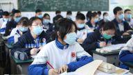 在教室里,学生们一边听老师讲解,一边记着笔记。
