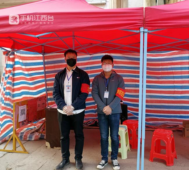 1 疫情防控期间,戴青峰(左一)在小区门口值守,引导居民有序进出。