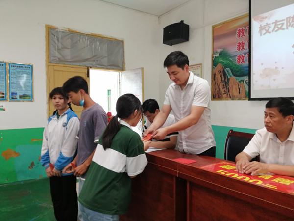 陈栋在为受助学生发放爱心助学红包