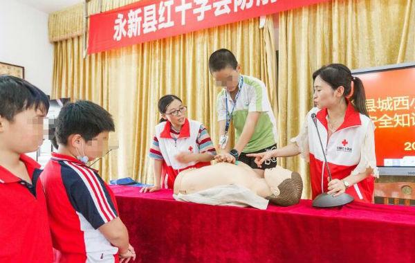 永新县红十字会应急救护培训师与城西小学学生互动学习。2