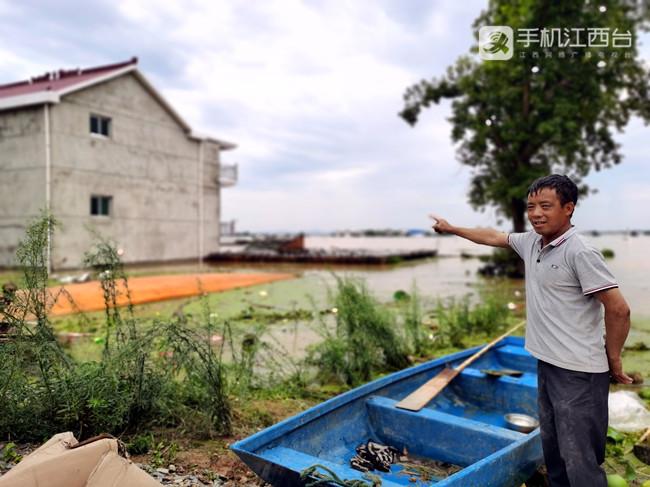 鄱阳县南湖村村民陈早生向记者指着自家被淹的房屋