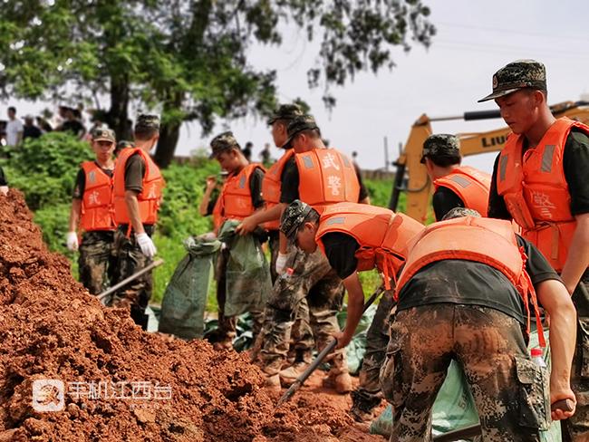 武警官兵在装填泥袋。记者陶望平 摄
