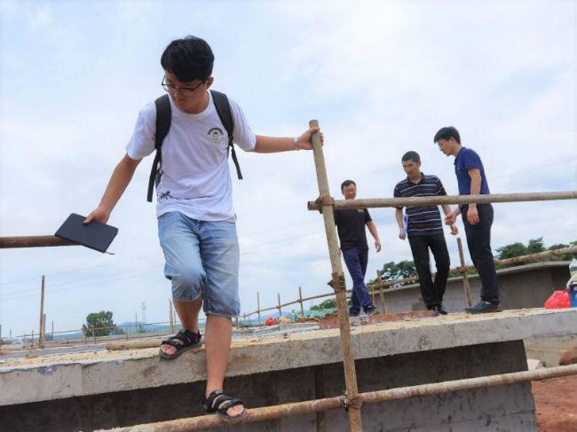 图为观察团成员跟随工作人员考察在建污水处理厂