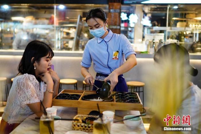 7月29日晚,云南昆明,一餐饮店服务员正在为顾客服务。 <a target='_blank' href='http://www.chinanews.com/' rel=