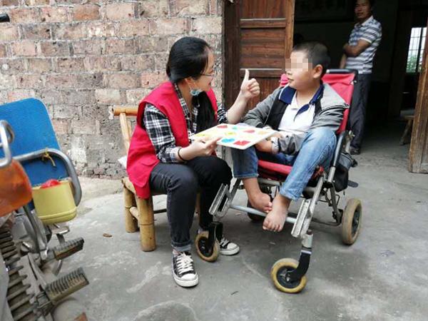 叶年华的儿子叶思同与送教下乡老师玩拼图游戏