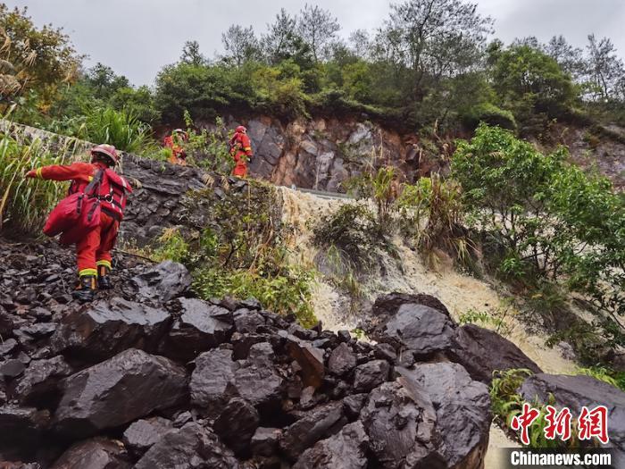 救援人员冒险沿着悬崖开辟生命通道 何立挺 摄