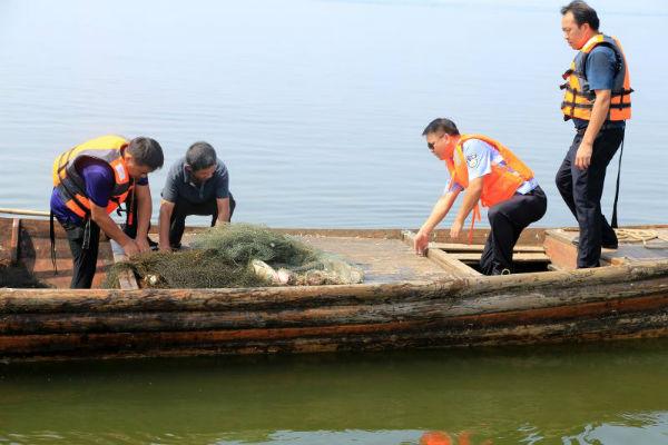 共青城市公安局民警对仍在水域违规作业的渔民进行法律知识宣讲