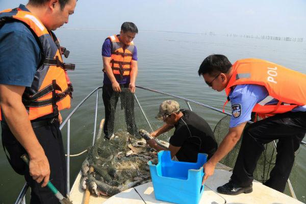 """共青城市公安局民警在鄱阳湖水面巡视中,发现一处用以捕鱼的""""迷魂阵"""",并对其进行清理"""