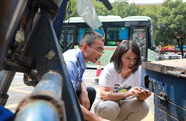 图为9月11日,民警和保险公司工作人员给电动三轮车采集车辆信息。