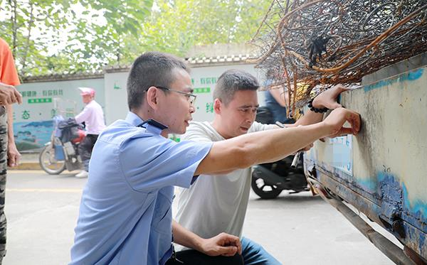 图为9月11日,民警帮助朱大爷的电动三轮车安装好车牌。