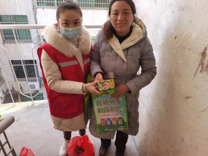 志愿者给居民发放活动纪念品