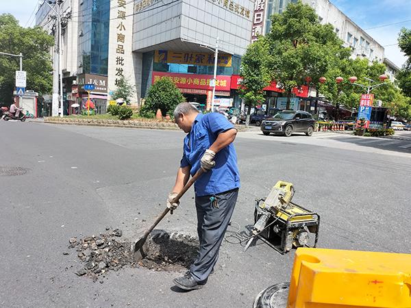 市政维修管理处顶着炎炎烈日,在马路上修复破损塌陷井盖,只为保障市民安全出行。