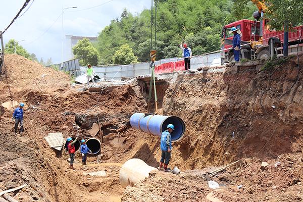 萍乡水务公司正在进行管道安装施工,为配合萍莲高速公路建设,施工人员烈日下吊装管道。