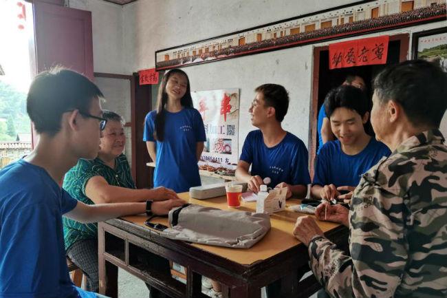 图3:医心筑梦服务团的志愿者入户为村民测血糖、血压