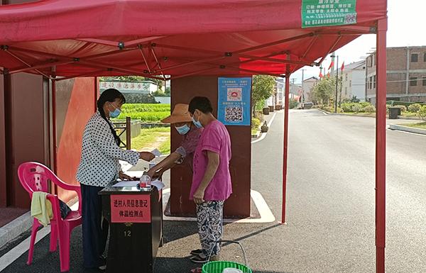 在沿背村體溫檢測點,志愿者劉金嬌正為村民測量體溫,查驗贛通碼。