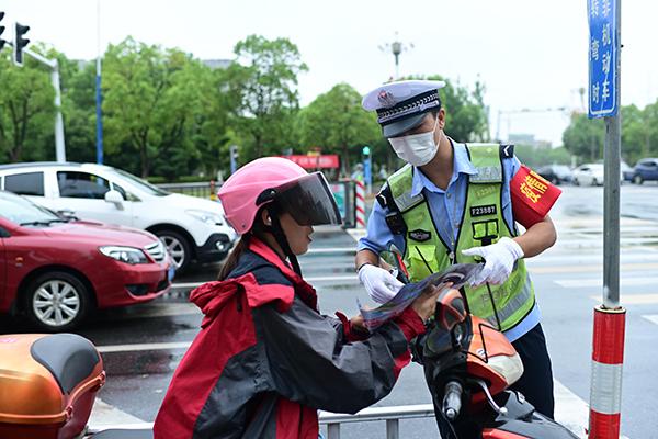 """图4:执勤交警在路面上对两轮车驾驶人宣讲""""一盔一带""""交通安全知识。"""