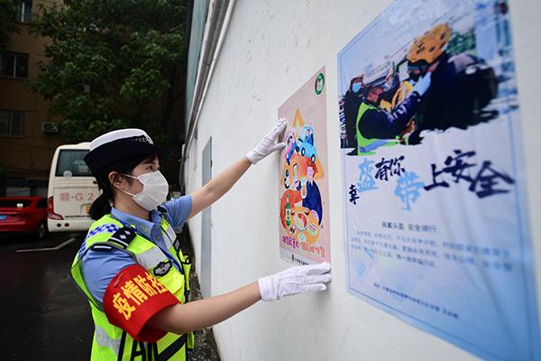图7:执勤交警在客运站张贴交通安全宣传海报,营造宣传氛围,努力提高群众文明出行意识。