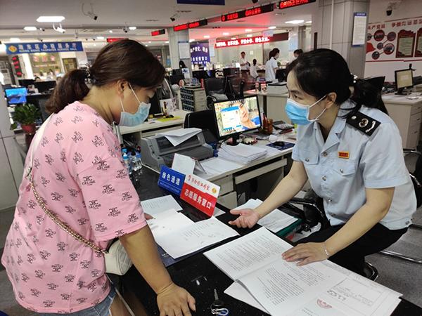(图为工作人员为纳税人讲解契税减免政策)