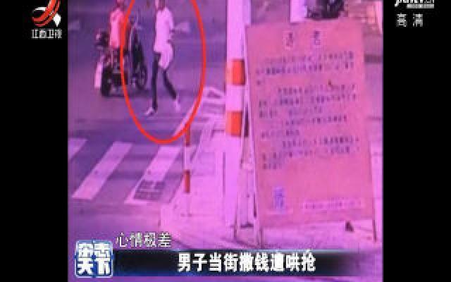 福建泉州一男子当街撒钱 引来路人哄抢