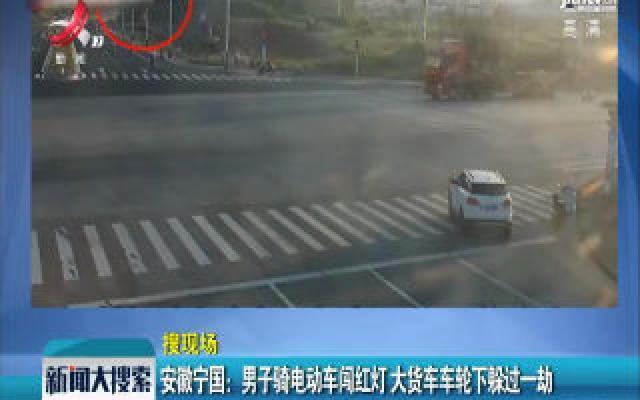 安徽宁国:男子骑电动车闯红灯 大货车车轮下躲过一劫