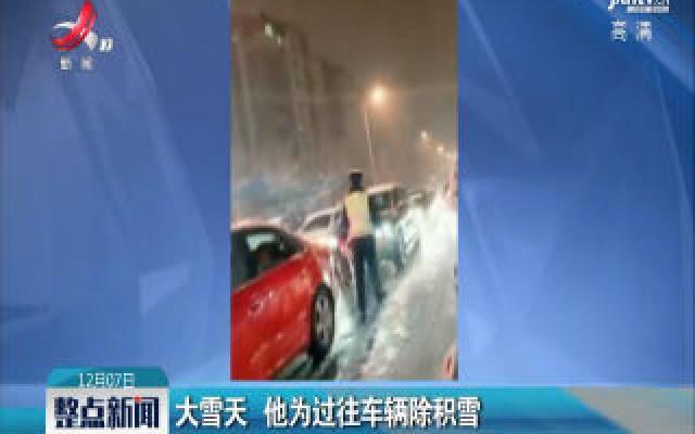 呼和浩特:大雪天 他为过往车辆除积雪
