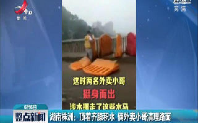 湖南株洲:顶着齐膝积水 俩外卖小哥清理路面