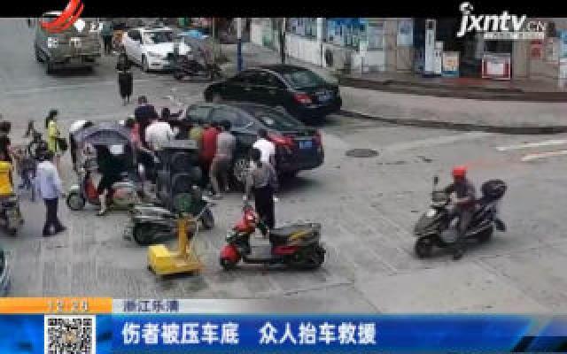 浙江乐清:伤者被压车底 众人抬车救援
