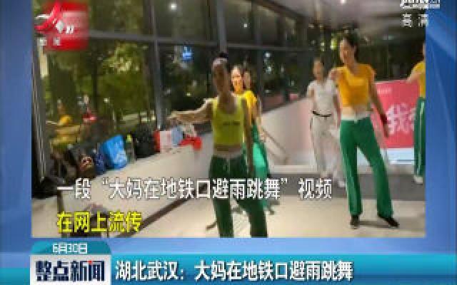 湖北武汉:大妈在地铁口避雨跳舞